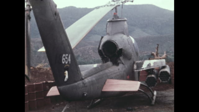 A pilot looks at the remains of a Cobra helicopter following an attack by North Vietnamese commandos Michael Fitzmaurice was awarded the Medal of...