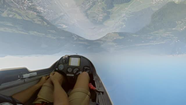 pov-pilot manövrieren des gleitschirms in der luft in der sonne auf den kopf tun stunts - segelflugzeug stock-videos und b-roll-filmmaterial