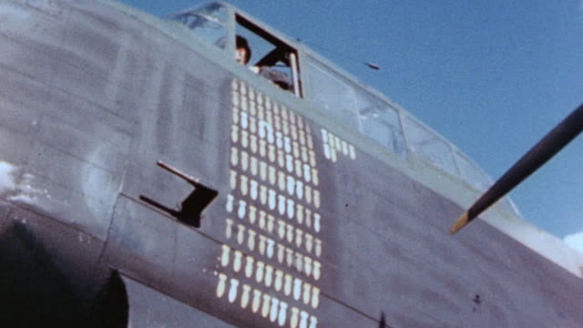 la pilot of raf lancaster heavy bomber giving thumbs up signal from cockpit with many mission tallies on side of fuselage - lancaster bomber stock videos & royalty-free footage