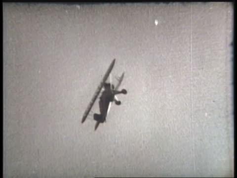 vidéos et rushes de a pilot performs stunts for a crowd at an airshow. - biplan