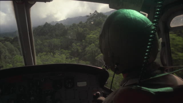 ms pan pilot piloting helicopter over rainforest - helicopter stock videos & royalty-free footage