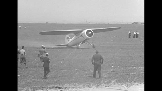 pilot ruth nichols in lockheed electra moving across airfield after landing group of men including photographers and probably reporters watching... - moving after stock videos & royalty-free footage