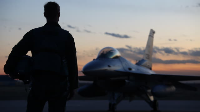 MS F-16 pilot silhouetted in front of F-16 fighter jet at sunset, Aurora, Colorado, USA