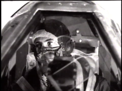 Pilot sitting in cockpit with oxygen mask on and view of P47 Thunderbolts in the air / European Theater of Operations