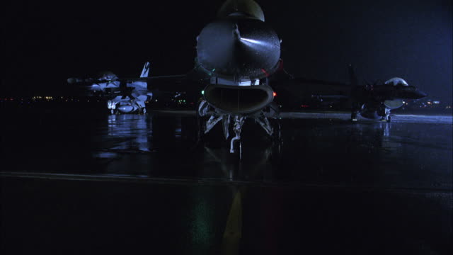 CS, ZI, ECU, Pilot sitting in stationary fighter jet at night, USA