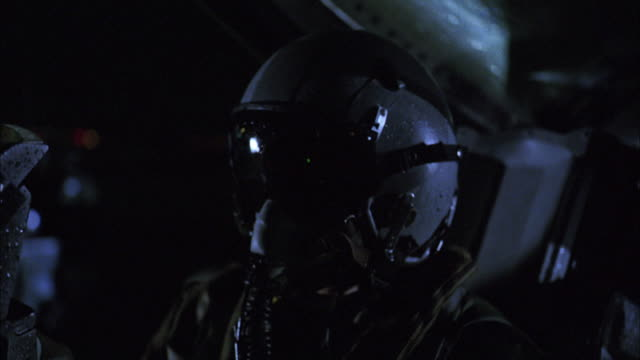 CU, Pilot sitting in stationary fighter jet at night, USA