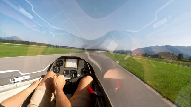 pov pilot sitting in the cockpit of a glider holding the control stick while being towed into the air - part of stock videos & royalty-free footage