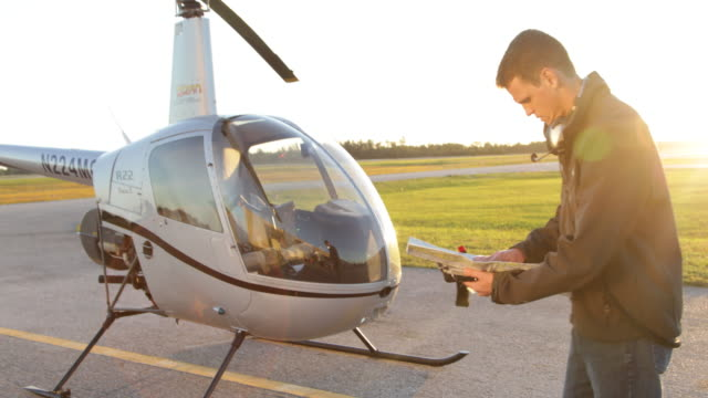 Pilot standing by helicopter looking at flight map.