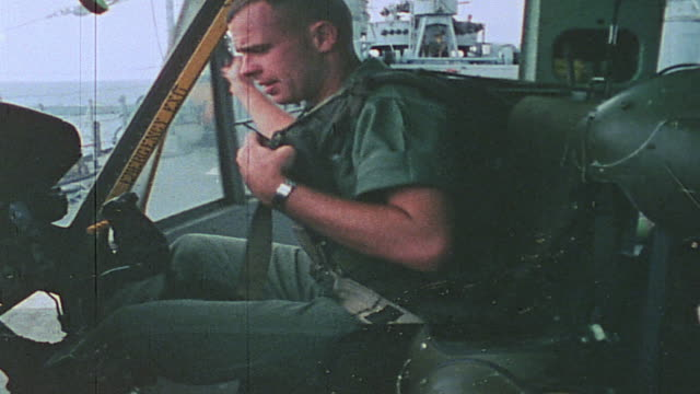 vídeos de stock, filmes e b-roll de pilot starting up helicopter gunship aboard uss harnett county during alert / vietnam - formato letterbox