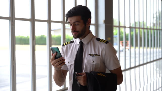 pilot stopped playing with his smartphone and smiles straight to camera. - pilot stock videos & royalty-free footage