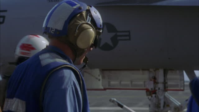 a pilot taxis an f-14 tomcat up to crew members on the deck of an aircraft carrier. - pilot stock videos & royalty-free footage