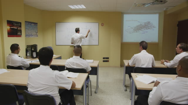 pilot training classroom, rear view of students to teacher in front of whiteboard, red r3d 4k - captain stock videos & royalty-free footage