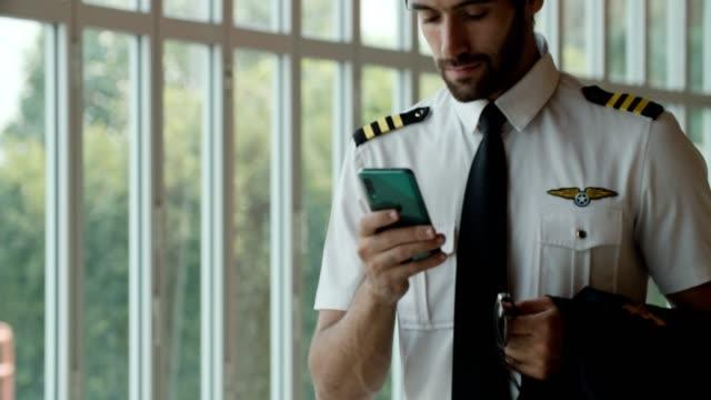 空港ターミナルでのスマートフォン使用パイロット - crew点の映像素材/bロール