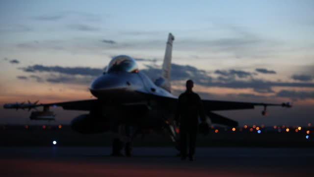 Ms F16 Pilot Walking Away From F16 Fighter Jet Into Light At Dusk