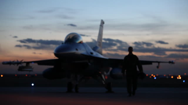 MS F-16 pilot walking away from F-16 fighter jet into light at dusk, Aurora, Colorado, USA
