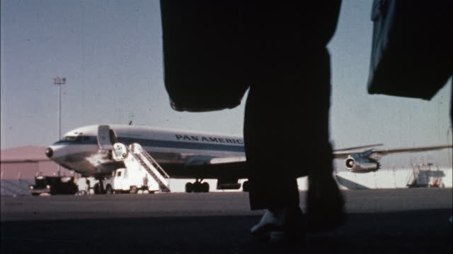 Pilots and flight attendants walk toward a parked Pan Am airliner on the tarmac.