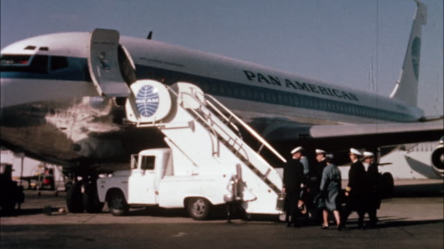 Pilots and flight attendants walk  up boarding stairs to the Pan Am airliner.