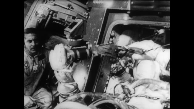 pilots charles conrad and richard gordon in gemini 11 space capsule / pilots hand on controls / view of earth with space / titan docks with agena... - titan moon stock videos & royalty-free footage