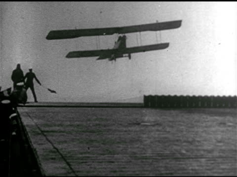 Pilots in biplanes trying to perfect landing on USS Langley tail hooks catching plane nosediving biplane partial cartwheel flipping off deck sliding...