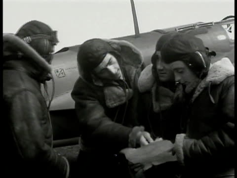 pilots in uniform standing looking at paper. pilot putting on hat. pilots in gear standing by plane paper. int two pilots in cockpit adjusting window... - 1940 stock videos & royalty-free footage