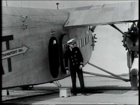 vídeos de stock e filmes b-roll de 1928 montage pilots preparing for flight and passengers boarding airplane / united states - 1928