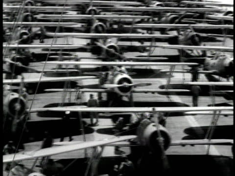 pilots walk to lines of airplanes on the deck of the aircraft carrier u.s.s. ranger. - 1931年点の映像素材/bロール