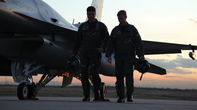MS F-16 Pilots walking next to an F-16 fighter jet at sunset, Aurora, Colorado, USA