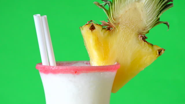 pina colada or piña colada cocktail slowly turning in display with green background - rum stock videos and b-roll footage