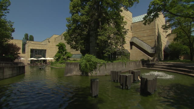 pinakothek der moderne, museum, architecture,  outdoor, dog in fountain, cafe, blue sky, panning shot, trees - cafe culture stock videos and b-roll footage