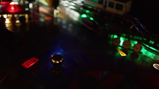 a pinball bounces around a lighted pinball machine - pinball machine stock videos & royalty-free footage