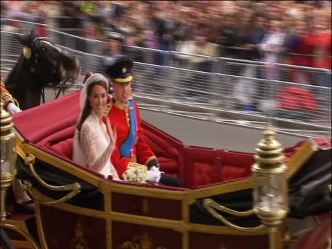 Pince William and Princess Catherine wave at crowds from the Royal carriage following their wedding service