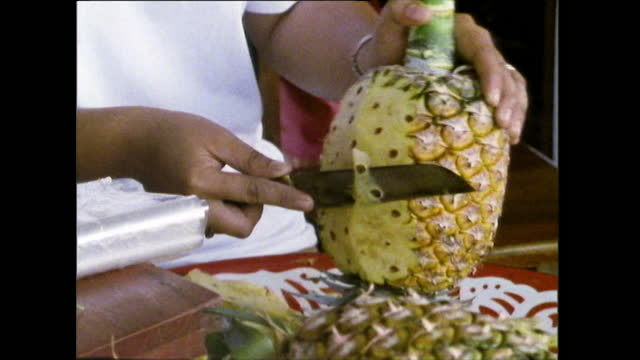 pineapple being peeled and carved in bangkok market; 1989 - bangkok stock-videos und b-roll-filmmaterial