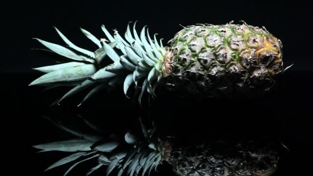 a pineapple emerges under dramatic shifting light. - chiaroscuro stock videos and b-roll footage