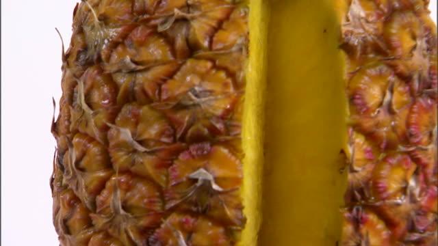 cu tu pineapple with missing slice rotating against white background / orem, utah, usa - bordsyteinspelning bildbanksvideor och videomaterial från bakom kulisserna