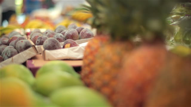 Pineapples and various colorful fruit on display in Brazilian market