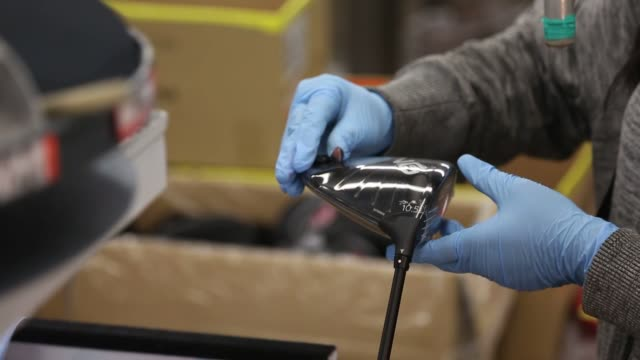 ping employees manufacturing and assembling golf club parts golf clubs heads sit in a mold while an employee applies a coat of oil to the clubface... - ゴルフクラブ点の映像素材/bロール