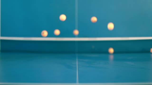 Ping-Pong balls falling on tennis table