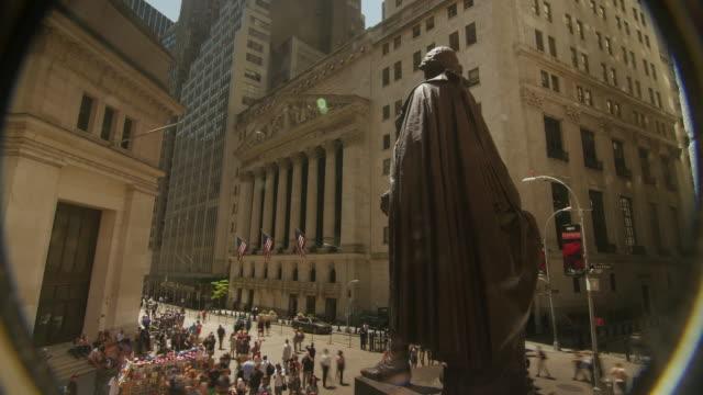 vídeos de stock e filmes b-roll de a pinhole view time lapse of new york stock exchange and george washington statue - george washington