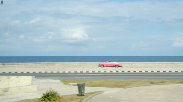 pink american classic car at havana malecon avenue. havana iconic image. on the move, dolly shot - cuba stock videos & royalty-free footage
