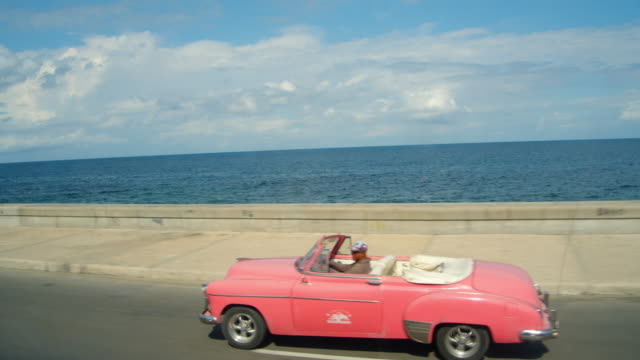pink american vintage car speeding down malecon road in havana. iconic image of cuba - cuba stock videos & royalty-free footage