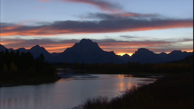 pink and blue clouds hover in the sky over the silhouettes of mt. moran and oxbow bend. - mt moran stock videos & royalty-free footage