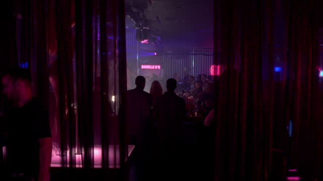 vidéos et rushes de pink and blue lights flash around pole dancers and patrons. - peep show
