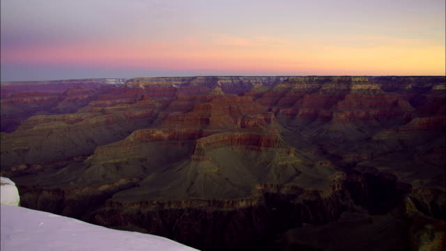 A pink and pale purple sky stretches above the Grand Canyon.