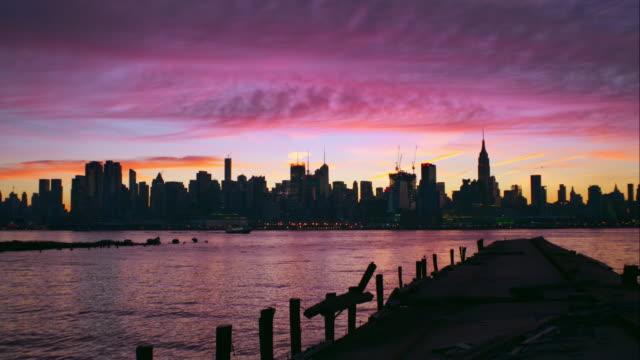 pink and purple clouds over midtown manhattan - 逆光点の映像素材/bロール