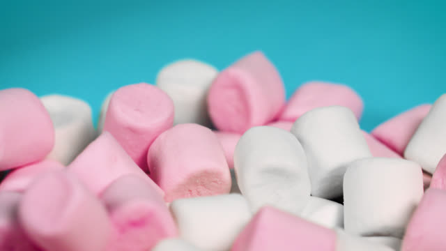vídeos y material grabado en eventos de stock de pink and white marshmallows slowly rotate in front of a blue background - marshmallow