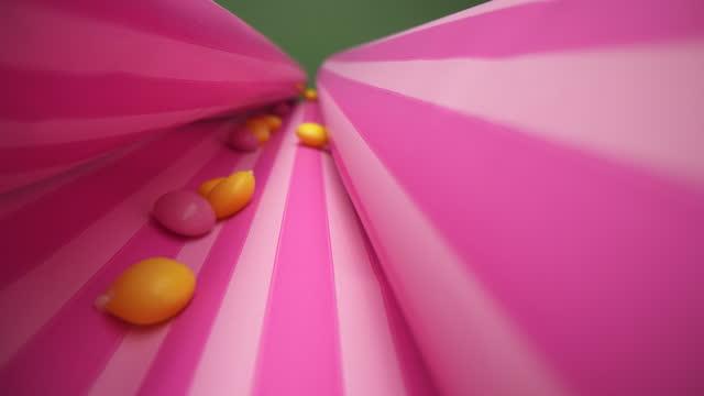 縞模様の包装紙にピンクと黄色のゼリービーンズ - ジェリービーンズ点の映像素材/bロール