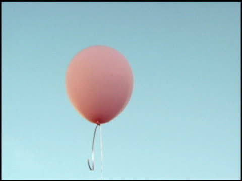 Pink balloon against blue sky.