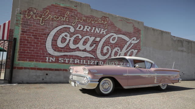 pink chevrolet driving in front on vintage coca cola mural - open stock videos & royalty-free footage