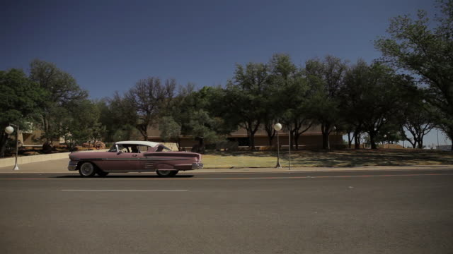 pink chevrolet passing on street in front of trees - horseless carriage stock videos & royalty-free footage