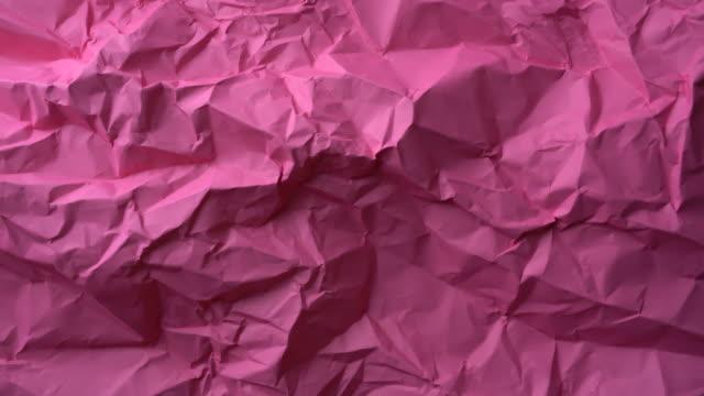 vídeos de stock, filmes e b-roll de papel amassado rosa girando - fundo rosa